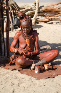 Himba Woman putting otjize on